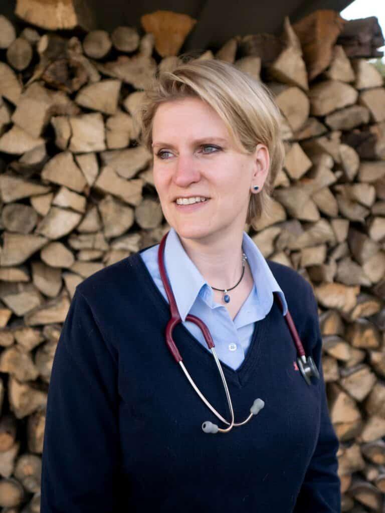 Tierärztin Dr. med. vet. Kathrin Kirschbaum sitzt vor gestapeltem Kaminholz